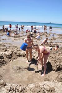Graben nach heissem Wasser am Hot Water Beach